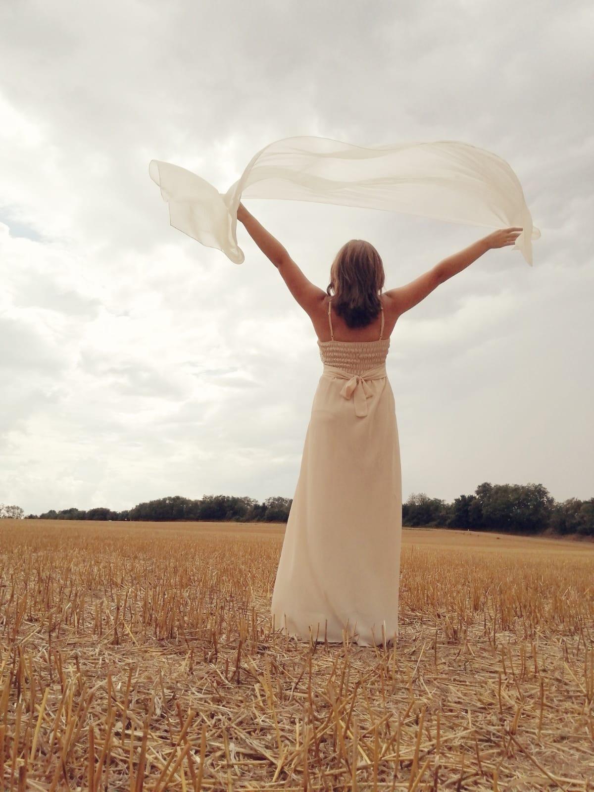 Mariée dans un champs avec son étole dans le vent - C&D Events - Wedding planner Oise et Paris
